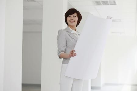 Businesswoman holding blueprint Stock Photo - 8259985