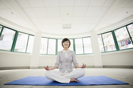 Businesswoman meditating on exercise mat Stock Photo - 8260587