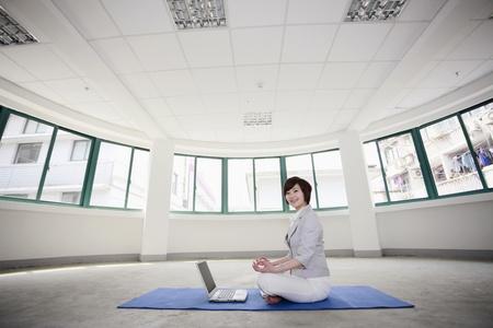Businesswoman meditating on exercise mat photo