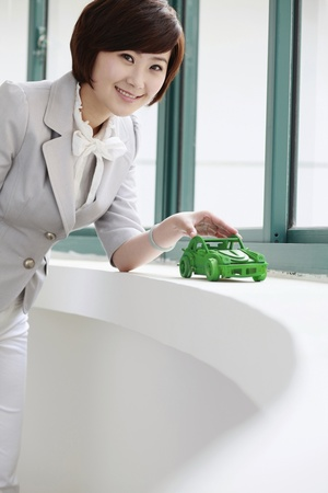 car model: Businesswoman playing with wooden car model Stock Photo