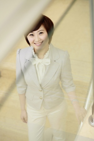 Businesswoman smiling while going down the stairs Stock Photo - 8260316