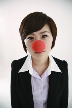 Businesswoman wearing a clowns nose looking at camera photo