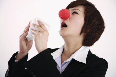 Businesswoman wearing a clown's nose about to sneeze into tissue Stock Photo - 8260295