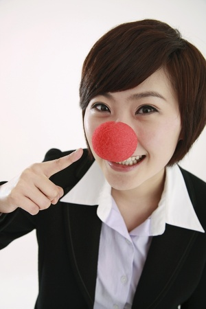 Businesswoman pointing at clown's nose Stock Photo - 8260392