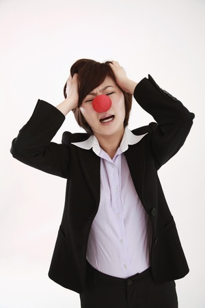 Businesswoman wearing a clowns nose with head in hands photo