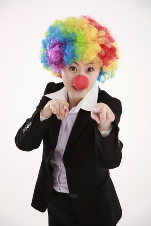 Businesswoman wearing a clowns wig and nose pointing with index fingers photo