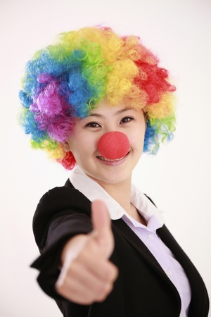 Businesswoman wearing a clowns wig and nose showing thumbs up photo