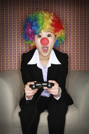 Businesswoman wearing a clown's wig and nose playing video game Stock Photo - 8260614