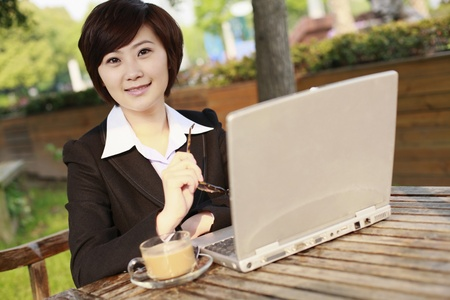 Businesswoman using laptop at an outdoor cafe photo