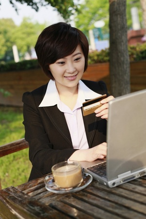 Businesswoman using laptop to shop online photo