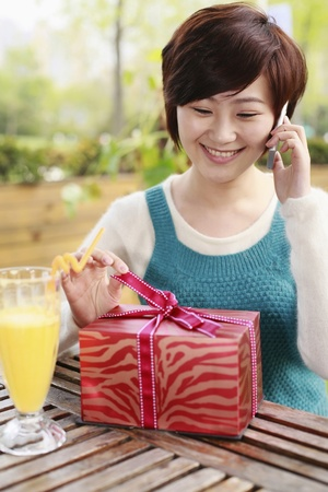 Woman holding ribbon at gift box while talking on the phone photo