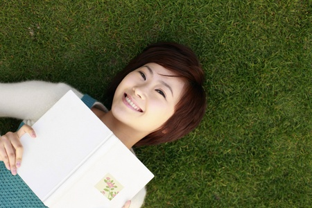 Woman lying on grass holding a book Stock Photo - 8260619