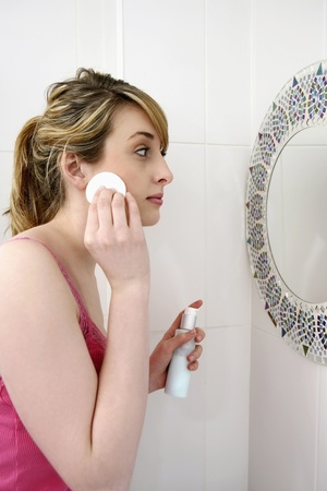 Woman applying lotion on face with cotton pad Stock Photo - 8260459