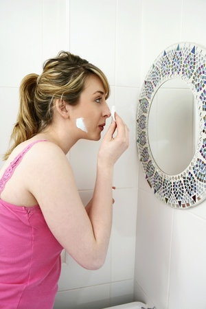 Woman applying lotion on face with cotton pad Stock Photo - 8260589