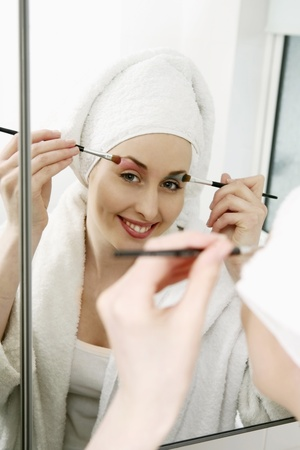 Woman applying make-up, towel on head photo