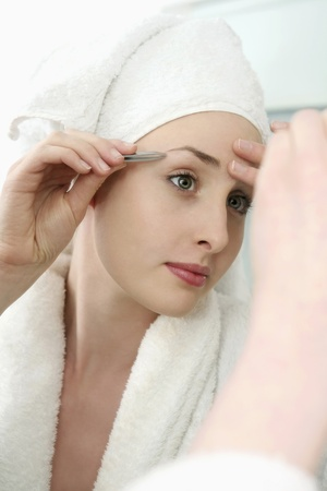 Woman plucking eyebrow with tweezers photo