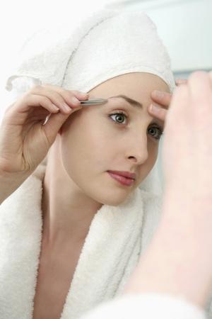 self conceit: Woman plucking eyebrow with tweezers