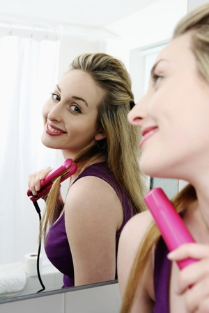 Woman using flat iron to straighten her hair photo