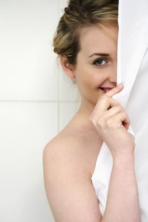 Woman hiding behind shower curtain photo