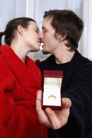 Man and woman embracing, man holding engagement ring Stock Photo - 8260016