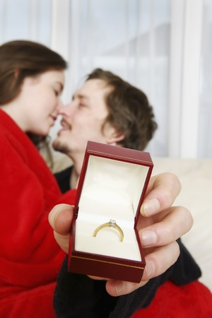 Man and woman embracing, man holding engagement ring Stock Photo - 8260022