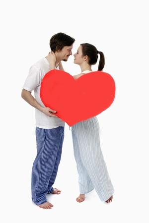 Man and woman embracing, man holding a heart shaped cushion photo