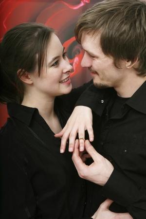 anillo de compromiso: Hombre posponiendo anillo en el dedo de la mujer