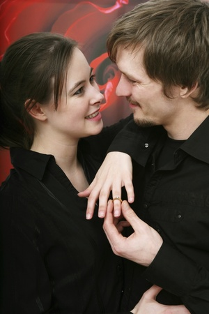 Man slipping engagement ring on womans finger photo