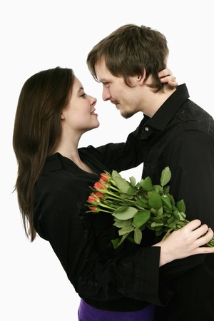 Man and woman embracing, woman holding flowers