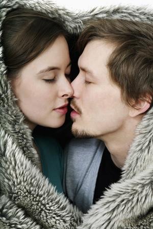 hombres besandose: Hombre y mujer bes�ndose en virtud de la manta