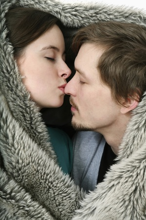 Man and woman kissing under the blanket photo