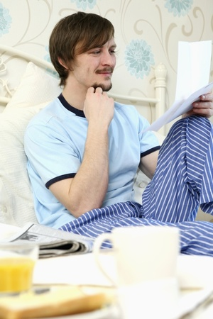 Man reading letter in bed Stock Photo - 8260346