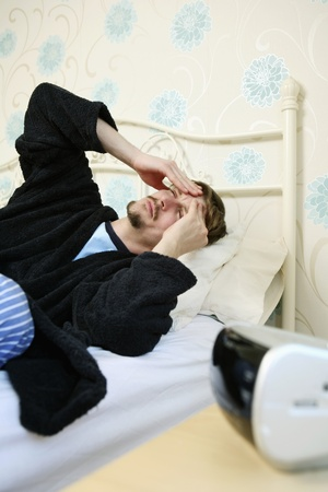 Man lying in bed with hands on head photo