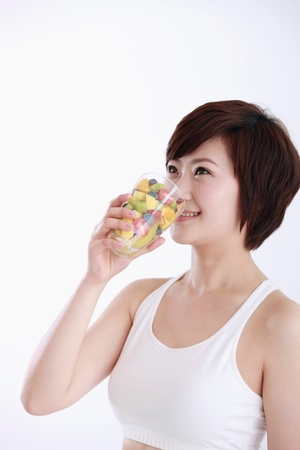 Woman drinking a glass of mixed fruits photo