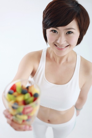 Woman holding a glass of mixed fruits photo