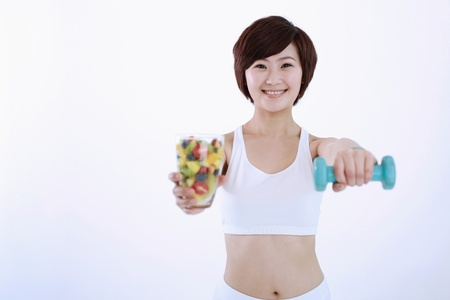 Woman holding a glass of mixed fruits and lifting a dumbbell photo