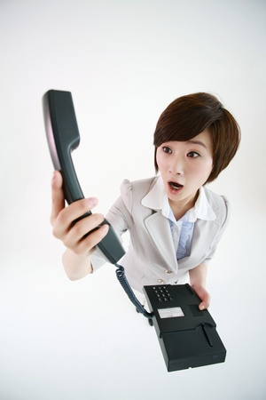 Businesswoman looking at telephone receiver photo