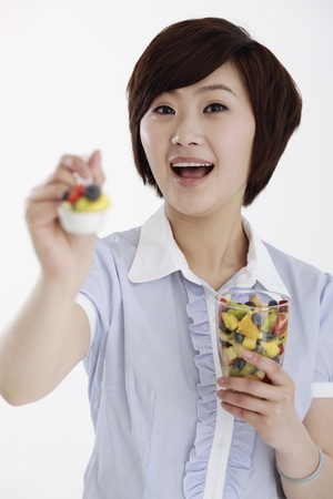 Businesswoman holding out a spoonful of mixed fruits photo
