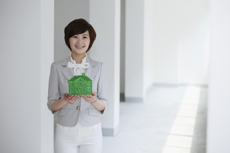 Businesswoman holding a wooden house model Stock Photo - 10570770