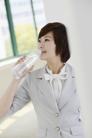 Businesswoman drinking water from plastic bottle photo