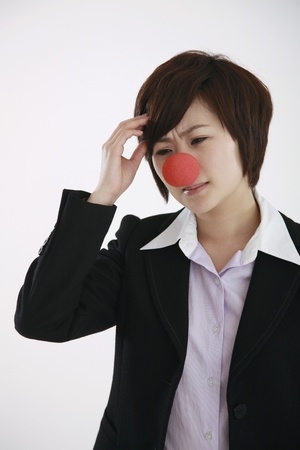 Businesswoman wearing a clowns nose with hand on head photo
