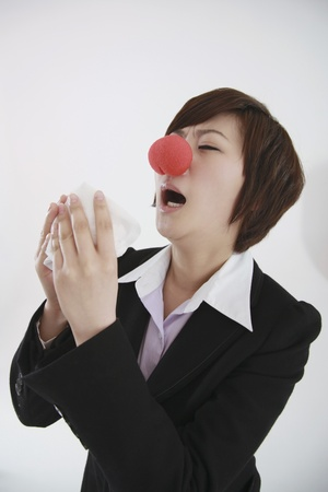 Businesswoman wearing a clowns nose about to sneeze into tissue photo
