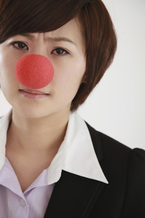 Businesswoman wearing a clowns nose frowning photo