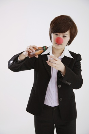 Businesswoman wearing a clowns nose taking cough syrup photo