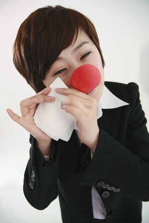 Businesswoman wearing a clowns nose wiping tears with tissue photo