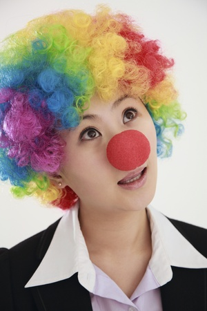 Businesswoman wearing a clowns wig and nose looking up photo