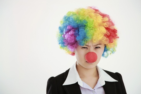 Businesswoman wearing a clowns wig and nose frowning photo
