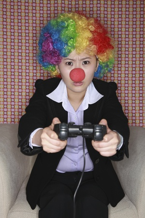 Businesswoman wearing a clowns wig and nose playing video game photo