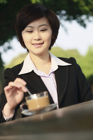 Businesswoman enjoying coffee at an outdoor cafe photo