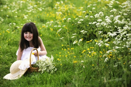 Girl in meadow picking flowers photo